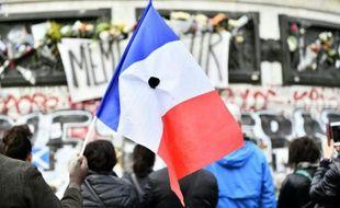 Un homme tient un drapeau français percé d'une fleur noire pendant la minute de silence en hommage aux victimes des attentats, place de la République le 16 novembre 2015