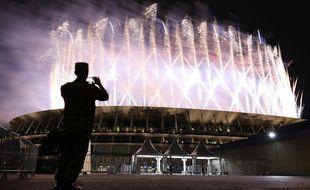 Un homme prend des photos du feu d'artifice illuminant le ciel du stade olympique lors de la cérémonie d'ouverture des Jeux olympiques de Tokyo 2020, à Tokyo, le 23 juillet 2021.