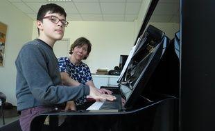 Arthur Piquemal et sa professeure de piano Anne Kablé-Lalande, lors d'u premier cours de piano pour personnes autistes, à Lille.