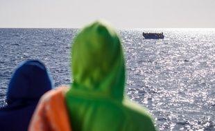 Deux migrants secoururs par un navire regardent une embarcation à secourir en Méditerranée.