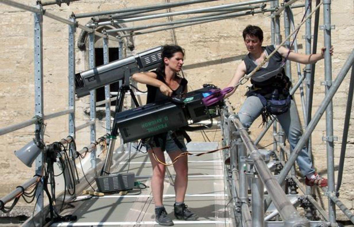 Deux techniciennes de plateau montent un projecteur en haut d'un échafaudage le 24 Juin 2002 dans la cour d'honneur du palais des Papes à Avignon. – AFP PHOTO BORIS HORVAT