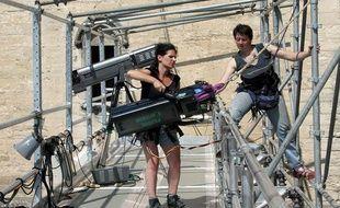 Deux techniciennes de plateau montent un projecteur en haut d'un échafaudage le 24 Juin 2002 dans la cour d'honneur du palais des Papes à Avignon.