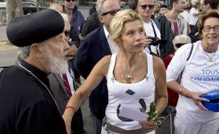French anti-gay marriage activist Virginie Tellene, also known as Frigide Barjot (C) and Bishop Abba Athanasios from the French Copte Orthodoxe church take part in a protest in support to the Christian populations in Iraq, on September 14, 2014 in Paris. Threats by jihadists have sent a fresh wave of Christians fleeing their Iraqi homeland, bustling from exodus to exodus in search of a safe haven to rebuild their lives.      AFP PHOTO / ALAIN JOCARD