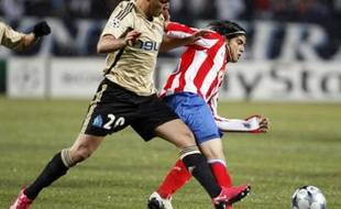 Olympique Marseille's Hatem Ben Arfa (L) challenges Atletico Madrid's Ever Banega during their Champions League soccer match at the Velodrome stadium in Marseille December 9, 2008. REUTERS/Jean-Paul Pelissier (FRANCE)