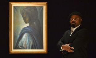 L'auteur nigérian Ben Okri pose à côté du portrait de la princesse Ife Adetutu Ademiluyi, le 7 février 2018.