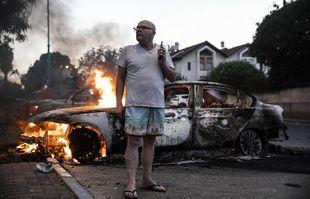 Un homme se tient à côté de sa voiture en feu à la suite d'affrontements entre des Arabes israéliens et la police dans la ville mixte de Lod, en Israël, le 11mai 2021.