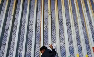Un homme s'accroche au mur qui le sépare des Etats-Unis, le long de la plage de Tijuana, au Mexique.