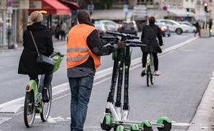 Un homme transporte plusieurs trottinettes pour aller les mettre en charge. Lime's.