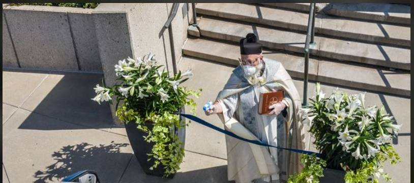 Le père en train d'arroser les fidèles d'eau bénite.