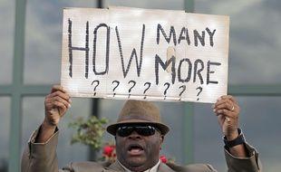 Le révérend Arthur Prioleau brandit une pancarte indiquant: «Combien d'autres encore?» lors d'une manifestation devant la mairie de North Charleston, en Caroline du Sud, le 8 avril 2015, après la mort de Walter Scott, abattu par un policier blanc.