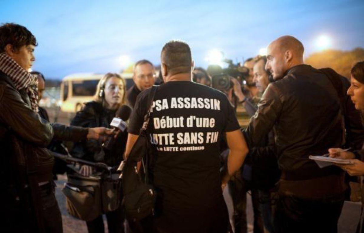 """Les ouvriers de PSA Peugeot-Citroën affluaient mardi matin à l'usine d'Aulnay-sous-Bois, doutant qu'un rapport sur le groupe, qui doit être publié dans la matinée, """"changera quoi que ce soit"""" à la fermeture prévue de leur usine. – Martin Bureau afp.com"""