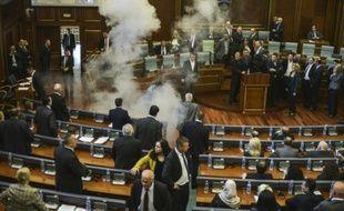 Les parlementaires se dispersent alors qu'un nuage blanc de gaz lacrymogène envahit le Parlement du Kosovo, le 15 octobre 2015 à Pristina