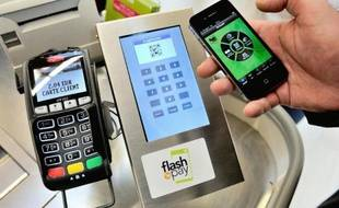 Un client paye avec son smartphone le 6 décembre 2012 dans un supermarché de Faches-Thumesnil, dans le Nord