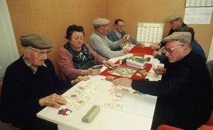 Des seniors jouent aux cartes dans un club du troisième âge.