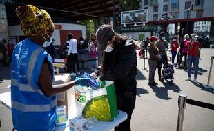 Des bénévoles du Secours Populaire distribuent des produits de première nécessité à Saint-Denis, le 6 mai 2020.