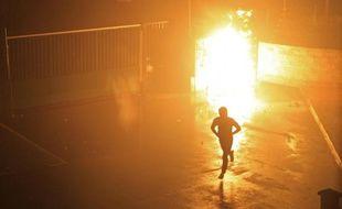 Un manifestant s'enfuit le 15 février 2016 après l'explosion d'un engin incendiaire à l'intérieur de la cour de la gendarmerie à Corte, en Corse