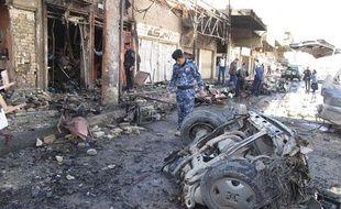 Un membre des forces de sécurité irakiennes inspecte le site d'un attentat à Hilla, en Irak, le 20 mars 2012.