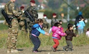Des enfants jouent près de soldats slovènes, devant la file de migrants et réfugiés venant de passer la frontière, le 26 octobre 2015