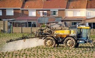 Un agriculteur traite un champ à proximité d'habitations.