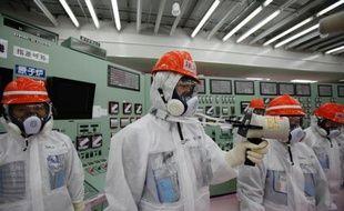 Photo du personnel de la firme japonaise Tepco en train de mesurer par dosimètre les radiations dans la salle de contrôle des réacteurs 1 et 2 de la centrale de Fukushima, le 10 mars 2014