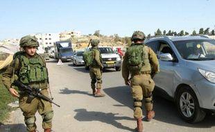 Des soldats israéliens contrôlent les véhicules à l'entrée de la ville de Hébron, le 23 novembre 2015 en Cisjordanie