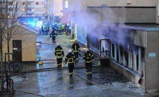 Des pompiers sur le site d'un incendie causé par un engin jeté de l'extérieur dans une mosquée du centre de la Suède, le 25 décembre 2014 à Eskilstuna
