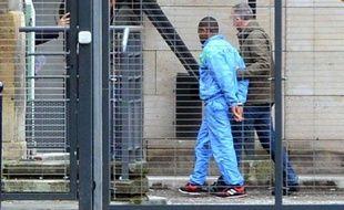 Le père (à g.) d'un bébé, qui affirme avoir jeté son enfant dans la Garonne, est escorté par un policier au palais de justice de Bordeaux, le 13 novembre 2014