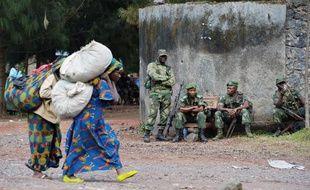 Des femmes passent devant des soldats de l'armée régulière congolaise, le 4 septembre 2013, près de Goma, dans l'est de la RDC
