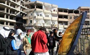 Une image du 24 décembre 2014 montrant des Syriens observant les débris d'un avion jordanien qui s'est écrasé dans la région de Raqa