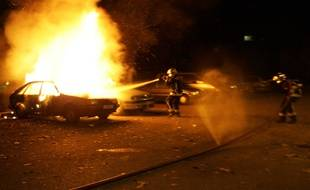 Des pompiers tentent d'éteindre un incendie lors des émeutes de 2005 à Clichy-sous-Bois.
