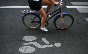 Une femme sur un vélo dans une voie réservée aux cycles.