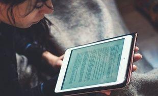 Une jeune fille en train de lire un e-book.