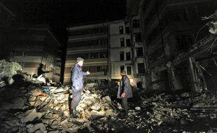 Des carabiniers italiens inspectent les décombres lors d'une patrouille nocturne, après le séisme dévastateur du 6 avril 2009 à L'Aquila.
