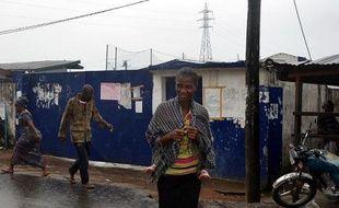 Des passants devant l'école qui sert de centre d'isolement des malades d'Ebola, le 17 août 2014 dans un quartier de l'ouest de la capitale Monrovia, au Liberia