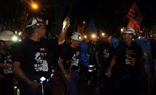 A la lumière de leurs lampes frontales, casque sur la tête, des centaines de mineurs espagnols en grève, venus à pied du nord du pays, ont parcouru mardi les rues de Madrid lors d'une marche nocturne pour protester contre la réduction des aides publiques.