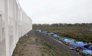 Des migrants installés dans une jungle, à Calais,  au pied des clôtures d'Eurotunnel.