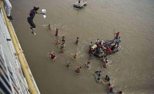 Des migrants honduriens sautent d'un pont bloqué à la frontière avec le Mexique pour continuer leur chemin vers le nord, le 19 octobre 2018.
