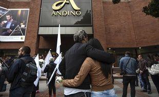 Des gens viennent se recueillir devant le centre commercial Andino.