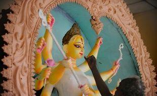 Un artiste peint une statue de déesse hindoue à Dacca le 29 septembre 2011