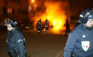 Des CRS délimitent un périmètre de sécurité autour de véhicules incendiés dans la nuit de la Saint-Sylvestre dans le quartier de l'Elsau à Strasbourg (archives).