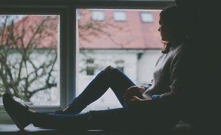 Une femme chez elle regarde par la fenêtre.