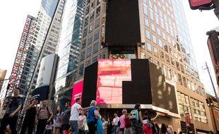 Les touristes s'arrêtent devant le panneau d'affichage endommagé par un incendie à Times Square, le 18 mai 2019.