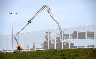 Des ouvriers installent le corridor sécurisé au port de Calais.