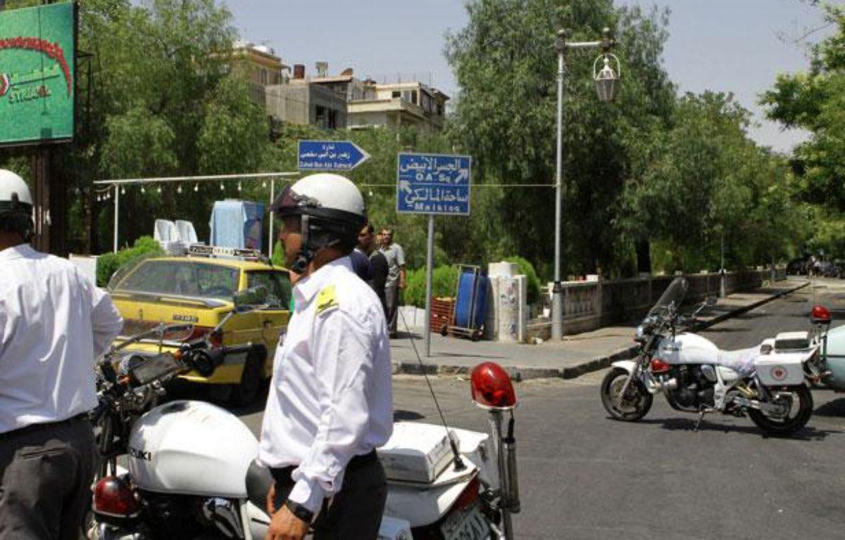La police syrienne monte la garde dans une rue proche du bâtiment de la Sécurité nationale visé par un attentat à Damas, le 18 juillet 2012. – AFP PHOTO\ STR