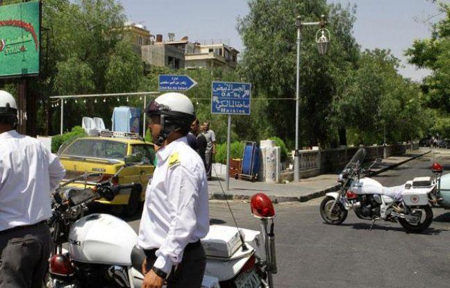 La police syrienne monte la garde dans une rue proche du bâtiment de la Sécurité nationale visé par un attentat à Damas, le 18 juillet 2012.