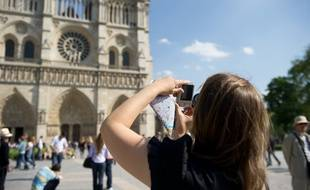 Une touriste sur  le parvis de la cathédrale Notre Dame de Paris.