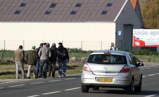 Des migrants sur une route près de Dunkerque, dans le Nord.