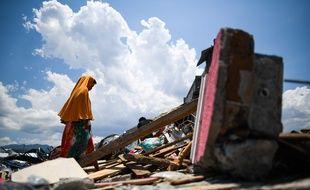 Une femme cherche des objets à récupérer dans les décombres après le séisme suivi d'un tsunami en Indonésie.