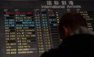 """Un homme se tient devant le panneau d'affichage des arrivées à Pékin le 8 mars 2014. Le vol Kuala Lumpur-Pékin est affiché """"en retard""""."""
