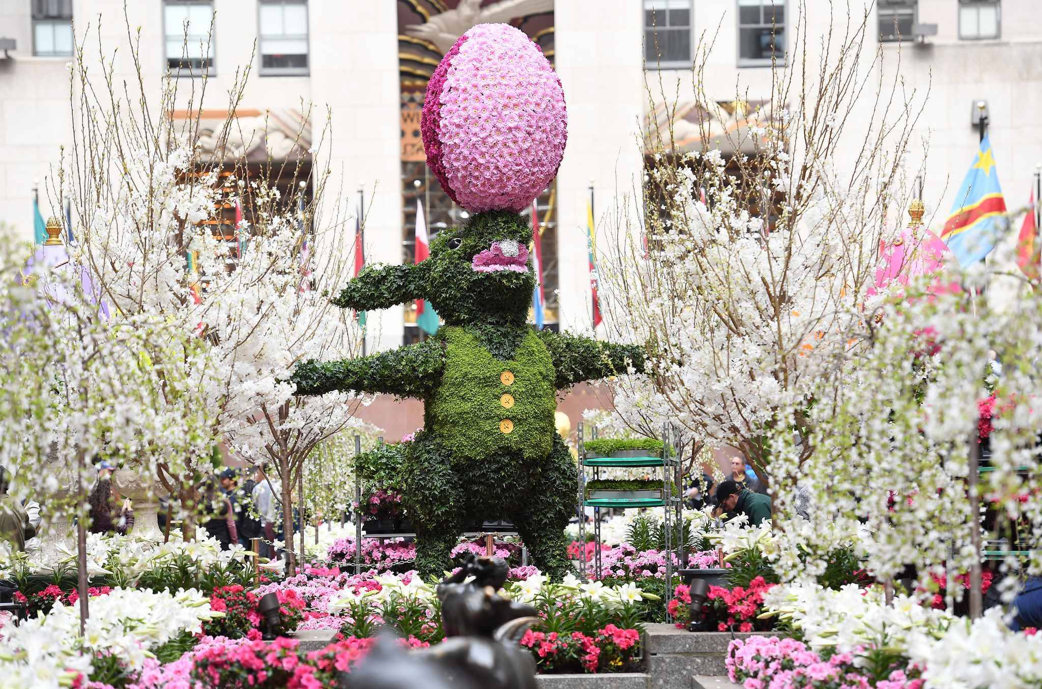 Thousands of white Easter Lilies are planted at the base of a 12-foot tall Easter bunny topiary made of moss and ivy, accompanied by an over-sized, multi-colored Easter egg made of daisies, in the Rockefeller Center Channel Garden on April 13, 2017 in New York City.